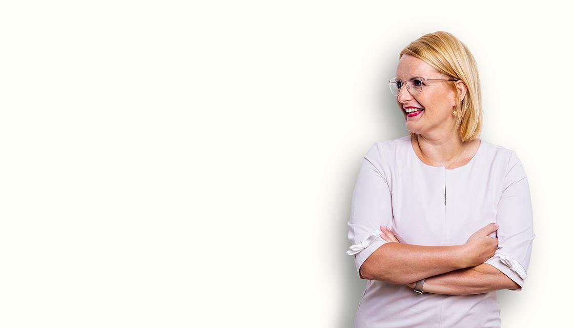 Silvia Zeller steht lächelnd vor einer Wand und blickt nach links